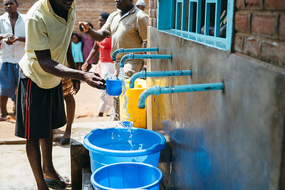 A man fills a cup at a community water kiosk in Malawi.