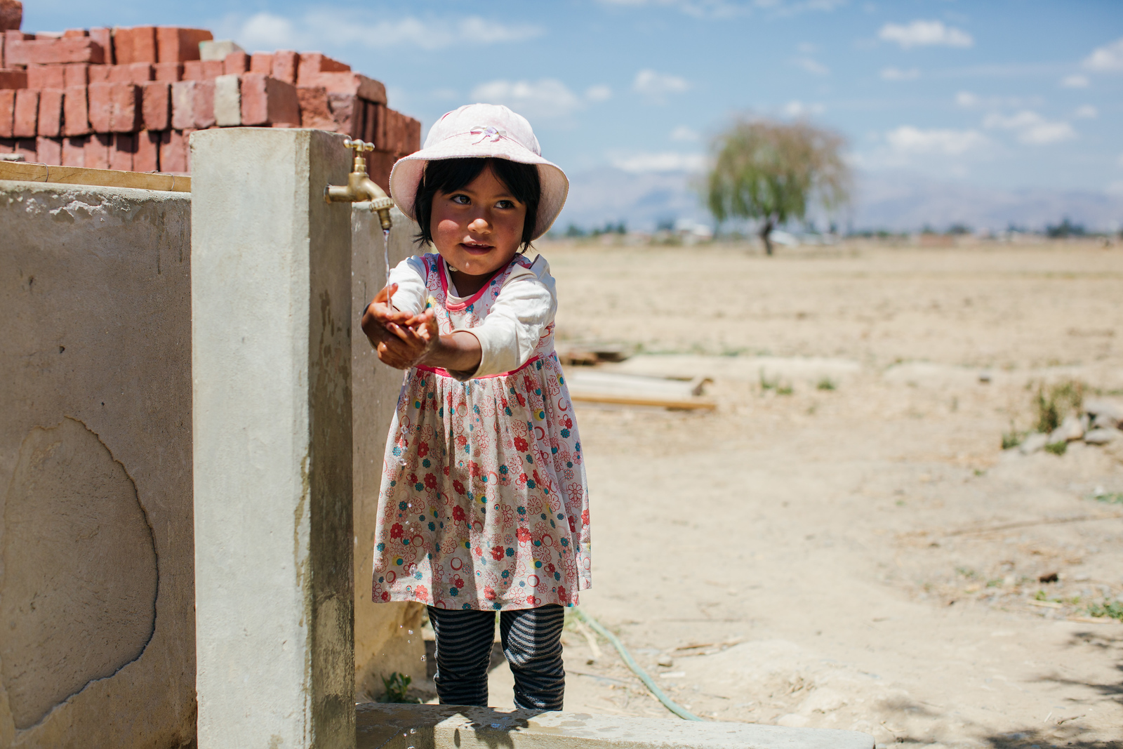 A young girl washes her hands at her family's water tap. Healthy handwashing habits instilled at a young age mean children grow up healthier (and happier!).
