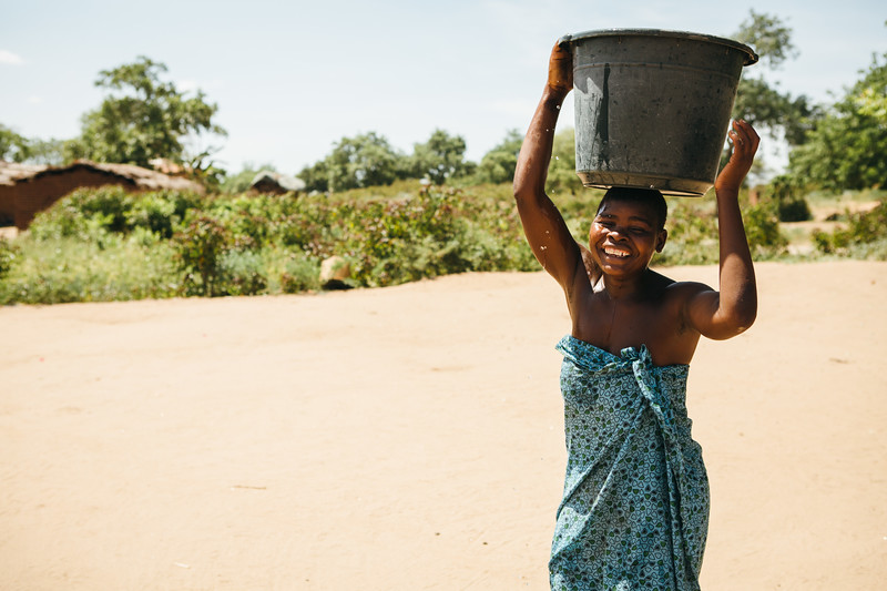 A woman carries a bucket of water in Chikwawa, Malawi.