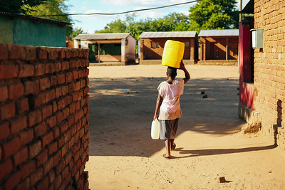 A child walks with water in their community in Chikwawa, Malawi.
