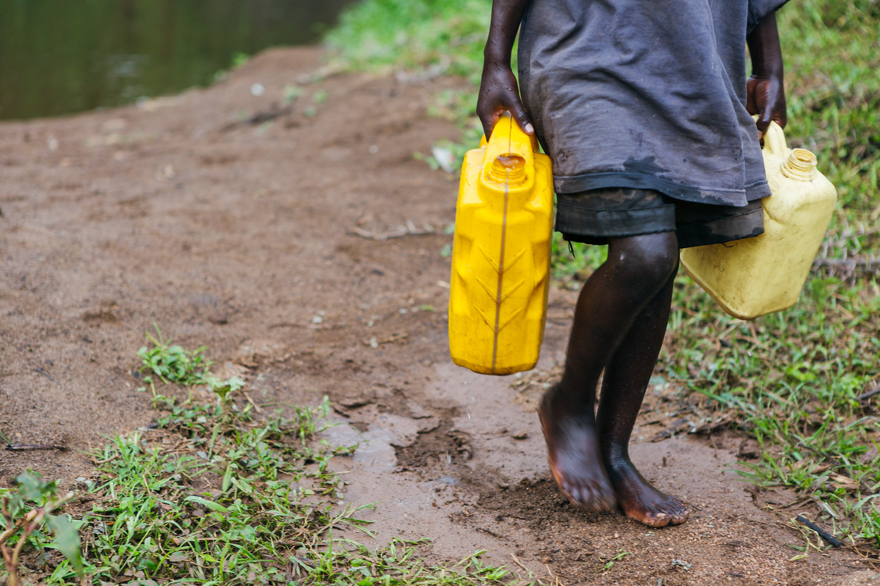 A child walking with jerry cans full of water.  Kids lose time they could be in school – arriving late, leaving early, and sometimes missing entire schooldays to fetch water.