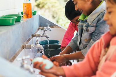 A group of girls wash their hands at a school in Guatemala.