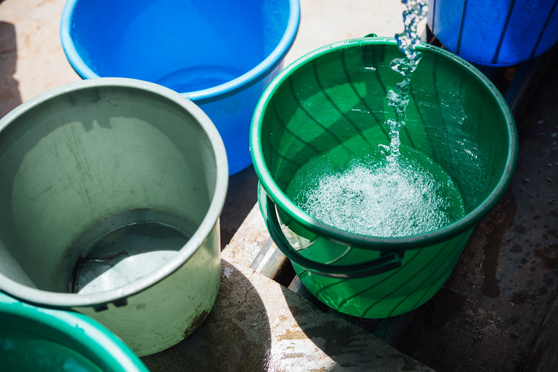 Buckets being filled with water at a water kiosk in Blantyre, Malawi.