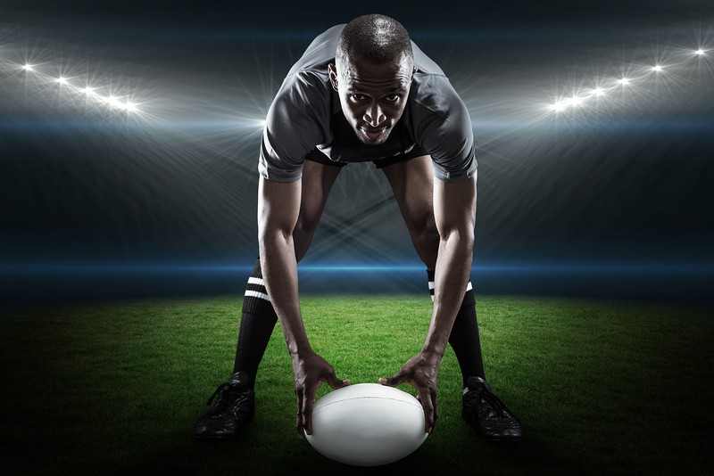 Composite image of portrait of sportsman holding ball