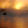 Anchored at Dawn<br /> <br /> A lonely sailboat in the mist at sunrise. I just missed the fish jumping in the foreground.