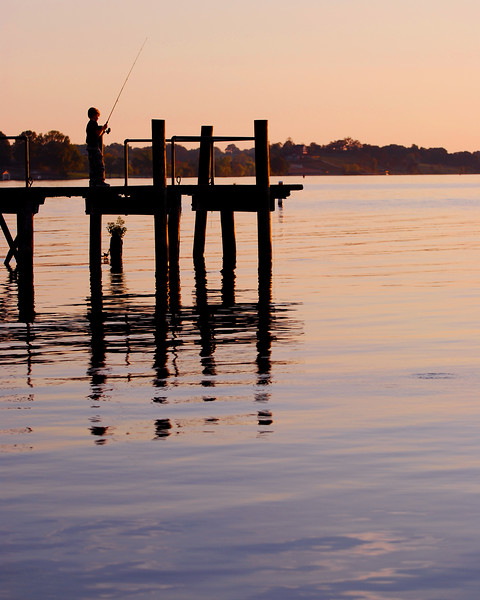 Fishing at Dusk<br /> <br /> I almost missed this shot. I was taking pictures of my Daughter playing in the water, and just happened to turn around as the little boy was reeling in his line for the last time.