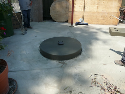 The new concrete pedestal for the fountain.  Note the steel plate and bolts.  We will mount the lower base to the plate, and then the fountain to the base.