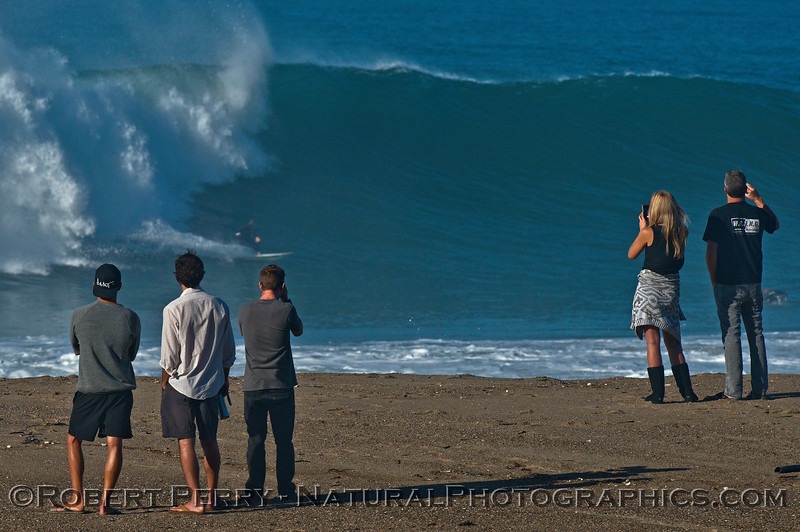 A big wave fan club enjoys the view - a surfer can be seen carving a turn as Hurricane Marie storm surf pounds Point Mugu - west side