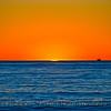 A sliver of sun - sunset on the open ocean with Platform Habitat silhouetted against the orange sky