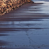 Horizontal drainage lines in the low tide sand.