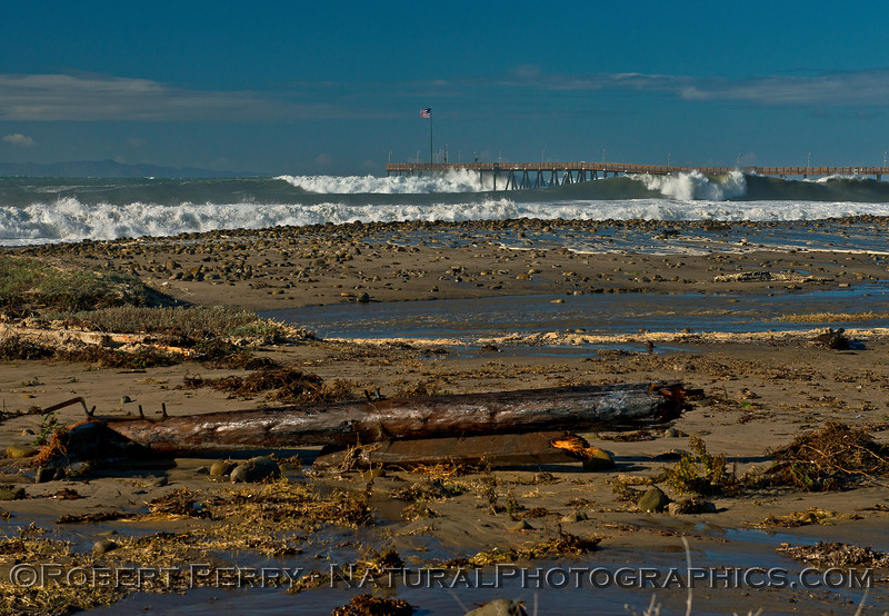 Broken pier piling on the beach, waves continue to pound Ventura Pier in the background.