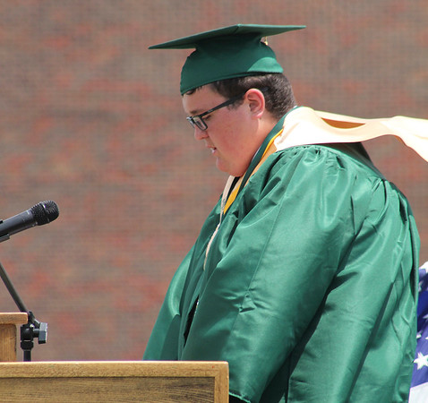 Roger Schneider   The Goshen News<br /> <br /> A brisk breeze blows the sash of Wawasee High School graduate Riley Menzie as he gives the student welcome speech to his classmates Sunday.