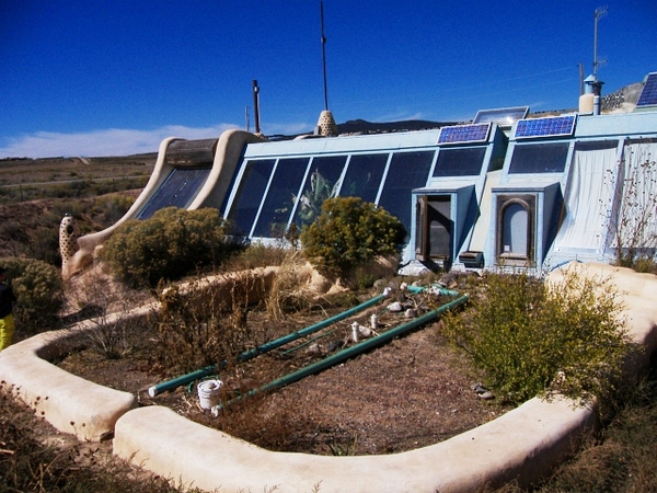 A lined mini-leach field receives and processes blackwater. (The drain pipes are exposed here for demonstration purposes only.) Non-food-bearing plants can safely be grown here.<br /> On the far left of the front face is the batch solar water heater.