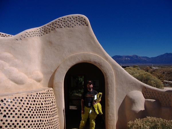 Main entrance to earthship HQ, complete with suspicious character.<br /> Note the use of recycled bottles in the walls. The bottles are meant to take space within the cement, creating a strong matrix.