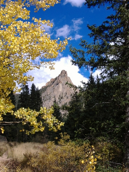 Golden Aspen trees and green spruce trees framing granite crags.