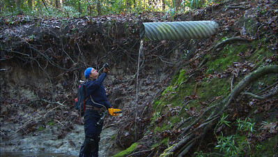 Jill Heinerth looks up into a stormwater pipe which is pouring into a local creek. Photo: Wes Skiles