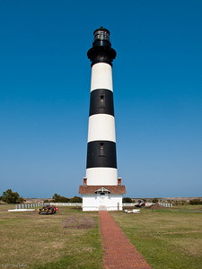 Bodie Island Lighthouse - Cape Hatteras National Seashore The lighthouse, first lit in 1872, is the third beacon to stand here.  The first one, built in 1848, sank on one side due to a poor foundation.  The second one, built in 1859, was blown up by Confederate soldiers during the Civil War.  The small building at the base of the lighthouse is the oil house where tanks of fuel (kerosene, whale oil, etc.) used to light the flame for the Fresnel lens at the top of the lighthouse were stored.