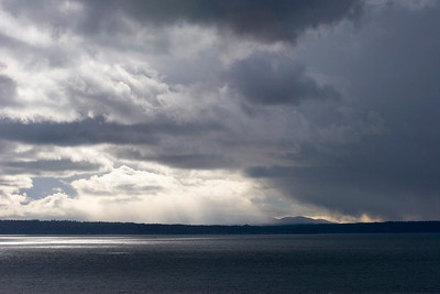 Sun rays through falling snow.  Photographed from Richmond Beach Saltwater Park, Shoreline, Wa