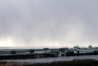 Edmonds ferry in the foreground, snow fall over the Puget Sound in the background.
