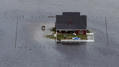 Floodwaters surround a house near Winnie, Texas after  Hurricane Ike, Sunday, Sept. 14, 2008. Ike was the first major storm to directly hit a major U.S. metro area since Hurricane Katrina devastated New Orleans in 2005.  (AP Photo/Pool, Smiley N. Pool)