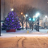 the holiday tree was still lit at Dickmann Town Center as the snow fell over the area Monday evening.