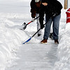 Jason and Stacy Biddle work together as they shovel the sidewalks around their house along Water Street in Chesterfield Tuesday morning.