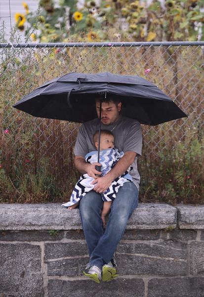 Baby under umbrella in rain 093014
