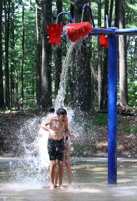 . Places to cool off: Manning State Forest in Billerica has walking trails and a Water Playground. Vincent Barbaro, 11, of Billerica, and his sister Makayla Barbaro, 13, rear, stand under a bucket of water at the Water Playground. (SUN/Julia Malakie)