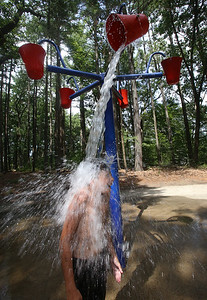 Places to cool off: Manning State Forest in Billerica has walking trails and a Water Playground. Vincent Barbaro, 11, of Billerica, stands under a tipping bucket of water at the Water Playground. (SUN/Julia Malakie)