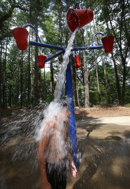 . Places to cool off: Manning State Forest in Billerica has walking trails and a Water Playground. Vincent Barbaro, 11, of Billerica, stands under a tipping bucket of water at the Water Playground. (SUN/Julia Malakie)