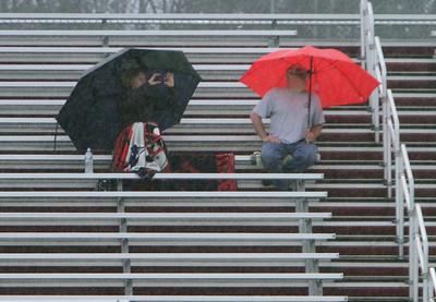 Bleacher spectators in rain 042216