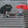 Spectators huddle under umbrellas in a heavy rain at the Chelmsford-Methuen girls lacrosse game. Trisha Hering, whose daughter Nicole plays for Methuen, and her brother-in-law Bob Valentine, both of Methuen, watch the game in the rain. (SUN/Julia Malakie)