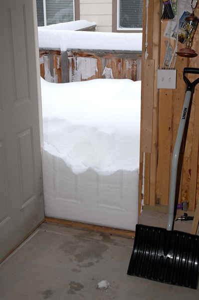 The snow shows an impression of the garage's side door.