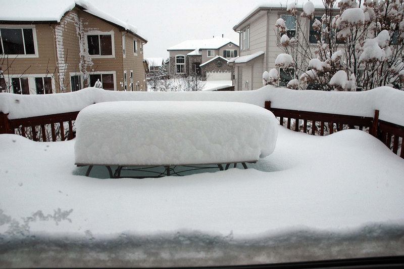"""Within 24 hours, the """"upslope"""" snowstorm had dumped about 2 feet in the Denver area. Looking out the kitchen window, there was a little snow on the bottom of the window frame, giving the illusion of very deep snow. It's only snow caked on the window frame itself. This is the patio table on the deck, with the drifted snow almost reaching the tabletop."""