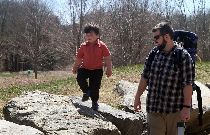Henry Tardif, 3, and his father Shaun Tardif of Nashua, walk along stone wall at Great Brook Farm State Park in Carlisle. (SUN/Julia Malakie)