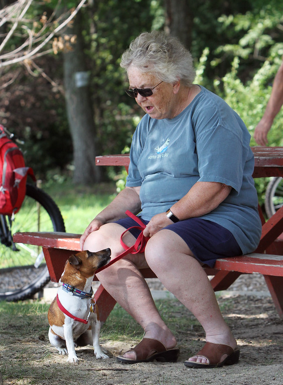 . Hot weather features. Linda Cooke of Ayer relaxes with her Jack Russell terrier, Mickey, 6, at Heart Pond in Chelmsford. (SUN/Julia Malakie)