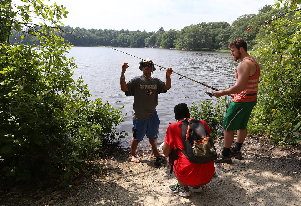 . Hot weather features. From left, Jake Randle, his brother Jonah Randle, and their friend Jon Lilly, all of Concord, fish for sunfish to throw back, at Heart Pond in Chelmsford. (SUN/Julia Malakie)
