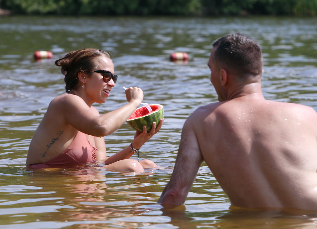 . Hot weather features. Samantha Baillargeon of Lowell chats with Tim Griffin of Billerica while they were both cooling off in 90-degree-plus weather at Heart Pond in Chelmsford. (SUN/Julia Malakie)