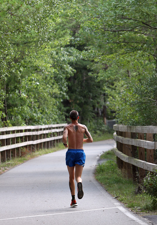 . Hot weather features at Heart Pond in Chelmsford. Ronaldo Motta of Lawrence runs on the Bruce Freeman Rail Trail. He\'s training for the New York Marathon in November. (SUN/Julia Malakie)