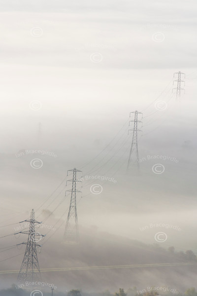 An aerial photo of electricity pylons sticking out of the fog.