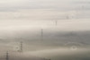 Aerial photo of electricity pylons sticking out of the fog.
