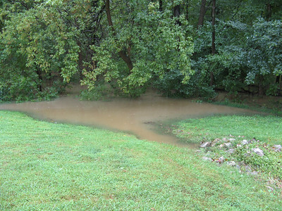 A swale between the houses is backfilling with brown floodwater.  9-7-11