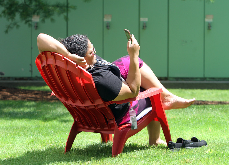 Lariza Balbuena of Methuen, who works in customer service at Verizon, enjoys her lunch break outside Cross Point on a not-too-hot sunny day. (SUN/Julia Malakie)