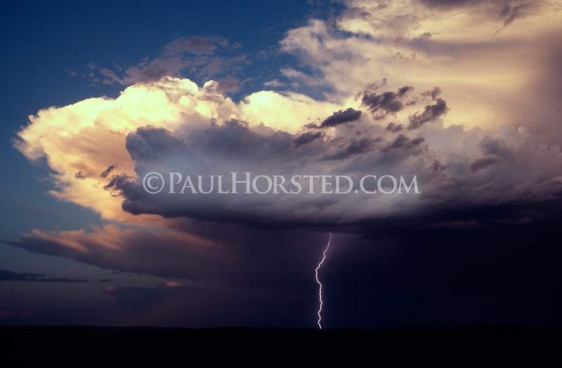 The setting sun highlights a storm cell with a single thunderbolt in western South Dakota. ©Paul Horsted, All Rights Reserved.