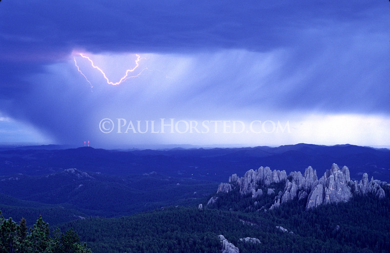 Lightning dances across the sky in a view from Harney Peak looking over the Cathedral Spires (right) and toward Mt. Coolidge (left, with red lights on towers).