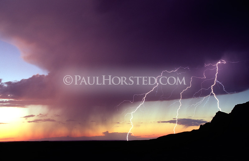 Sunset forms a backdrop for rainshowers and lightning in Badlands National Park in South Dakota. ©Paul Horsted, All Rights Reserved.