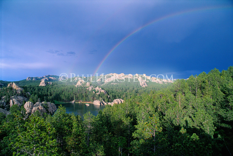 A rainbow arcs across the sky above Sylvan Lake in Custer State Park, in the Black Hills of South Dakota. Harney Peak is visible in the distance at left.