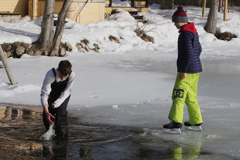 Features at frozen Long Lake in Littleton. Brayden Hood, left, fishes a hockey puck out of shallow water as his friend Nick Sloboda watches. Both are 12 and from Littleton. (SUN/Julia Malakie)