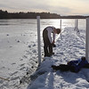 Features at frozen Long Lake in Littleton. Brayden Hood, 12, of Littleton, puts gloves back on, after fishing a hockey puck out of shallow water. (SUN/Julia Malakie)