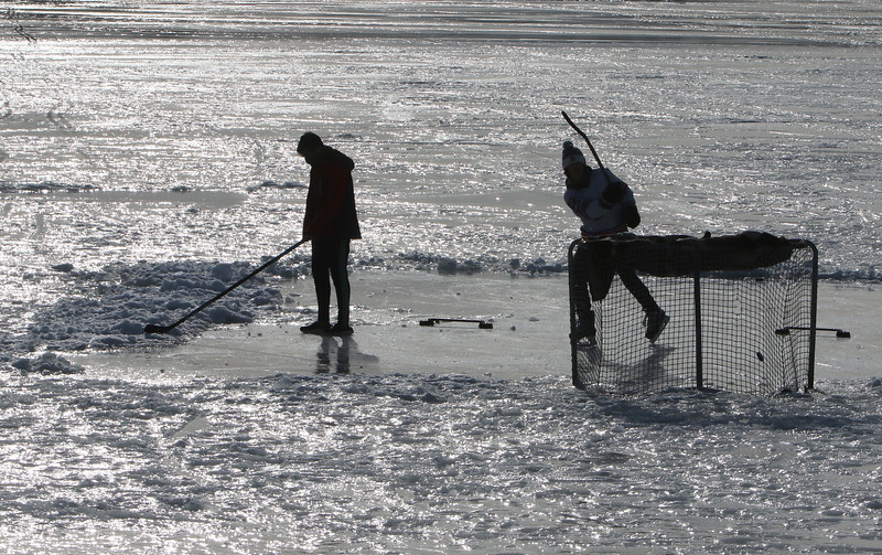 Features at frozen Long Lake in Littleton. Jack Borges, 14, of Littleton, left, and his hockey friend Nathan LoConte, 14, of Westford, use one of the smooth ice patches on Long Lake. (SUN/Julia Malakie)